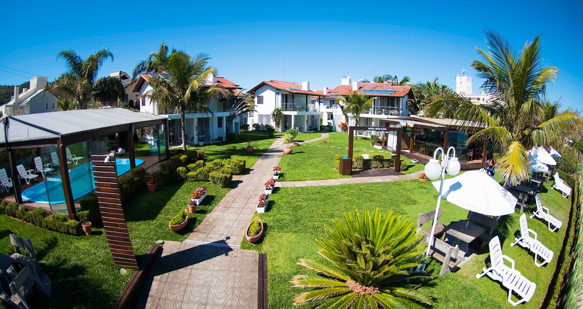 Belo e vasto gramado com flores em frente às ilhas do Hotel Sete Ilhas, e um restaurante também à beira mar de Jurerê em Florianópolis.