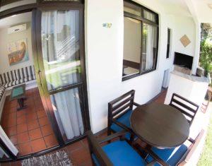 Área externa das ilhas 3 e 5 no hotel Sete Ilhas em Florianópolis com churrasqueira, mesa e cadeiras