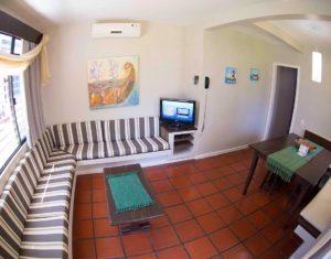 Sala de estar das ilhas 3 e 5 do Hotel Sete Ilhas em Jurerê com mesa de jantar, ar condicionado e televisão a cabo