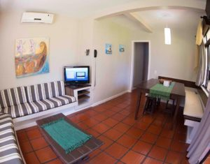 Visão completa da sala de estar e jantar integrada das ilhas 3 e 5 do hotel Sete Ilhas em Jurerê, Florianópolis
