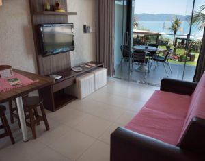 A sala de estar da suíte superior do Hotel Sete Ilhas em Florianópolis tem uma sala de estar moderna e aconchegante junto à sacada de frente para o mar de Jurerê