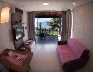 Visão da sala de estar integrada com cozinha e a sacada com vista para o mar de Jurerê na suíte superior do Hotel Sete Ilhas em Florianópolis, Santa Catarina.