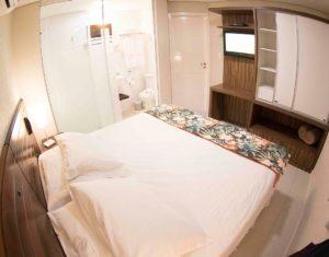 Quarto completo com televisão a cabo, banheiro, armário, telefone e ar condicionado split na suiíte superior do Hotel Sete Ilhas em Florianópolis.