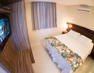 Visão do quarto completo com ar condicionado e televisão a cabo na suiíte superior do Hotel Sete Ilhas em Jurerê, Santa Catarina.