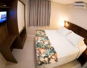 Quarto de casal com armário, televisão a cabo e ar condicionado em ambiente moderno e confortável no hotel Sete Ilhas em Florianópolis, Santa Catarina