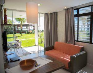 Bela sala de estar com ótima iluminação, janelas e portas grandes de vidro, televisão a cabo, mesa para dois e sofá aconchegante no hotel Sete Ilhas em Florianópolis, com vista para o mar.