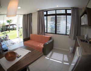 A sala é integrada com a cozinha, que possui microondas e frigobar. Conforto e conveniência à beira mar de Jurerê em Florianópolis no hotel Sete Ilhas!