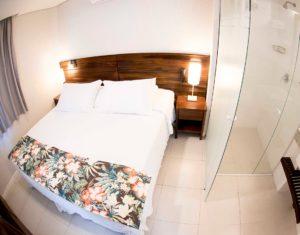 Ângulo com banheiro e box de vidro e a cama de casal da suíte térra do hotel Sete Ilhas em Jurerê, Florianópolis.