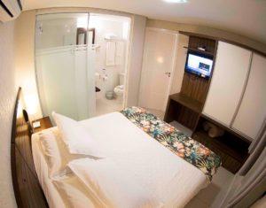 Suíte térrea vista de um dos cantos do quarto, incluindo banheiro, armário, televisão a cabo e ar-condicionado no hotel Sete Ilhas em Jurerê!