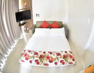 Sofá cama em sala com cortinas fechadas; o Hotel Sete Ilhas em Florianópolis tem sofá camas em diversas de suas unidades.